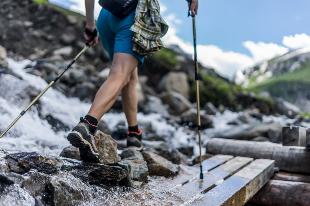ground level view of hiker with trekking poles crossing a rocky river