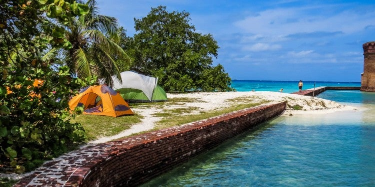 Brick and cement wall running alongside Floridian ocean with tent and trees on top of wall