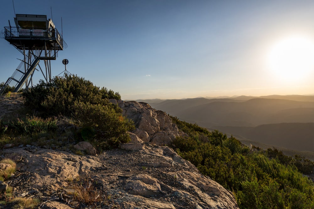 View of fire tower on rocky hillside with rolling mountains in background