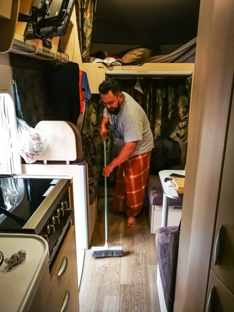 man sweeping inside his RV