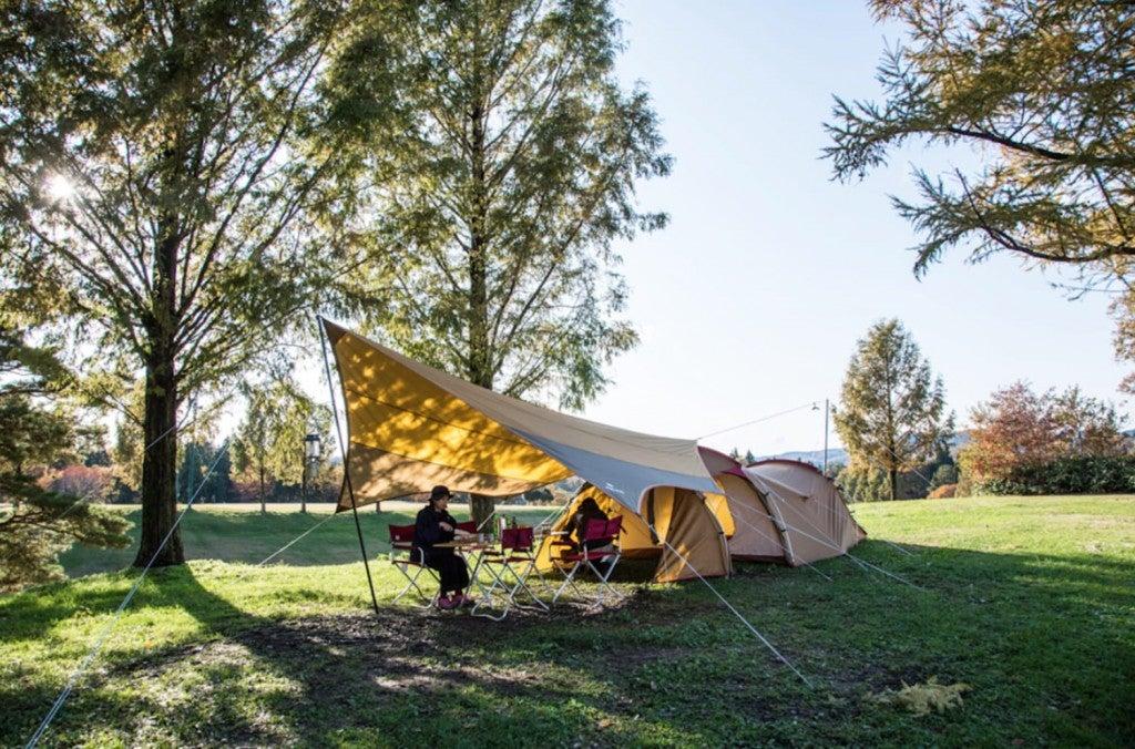 woman preparing food beneath snow peak tent and tarp family setup