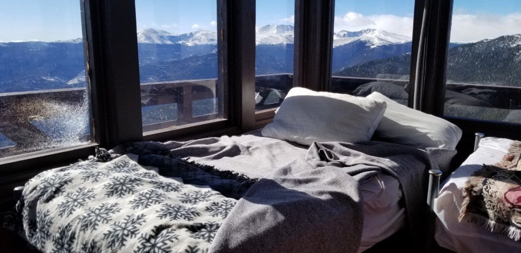photo of bed in fire tower overlooking snow capped mountains in colorado