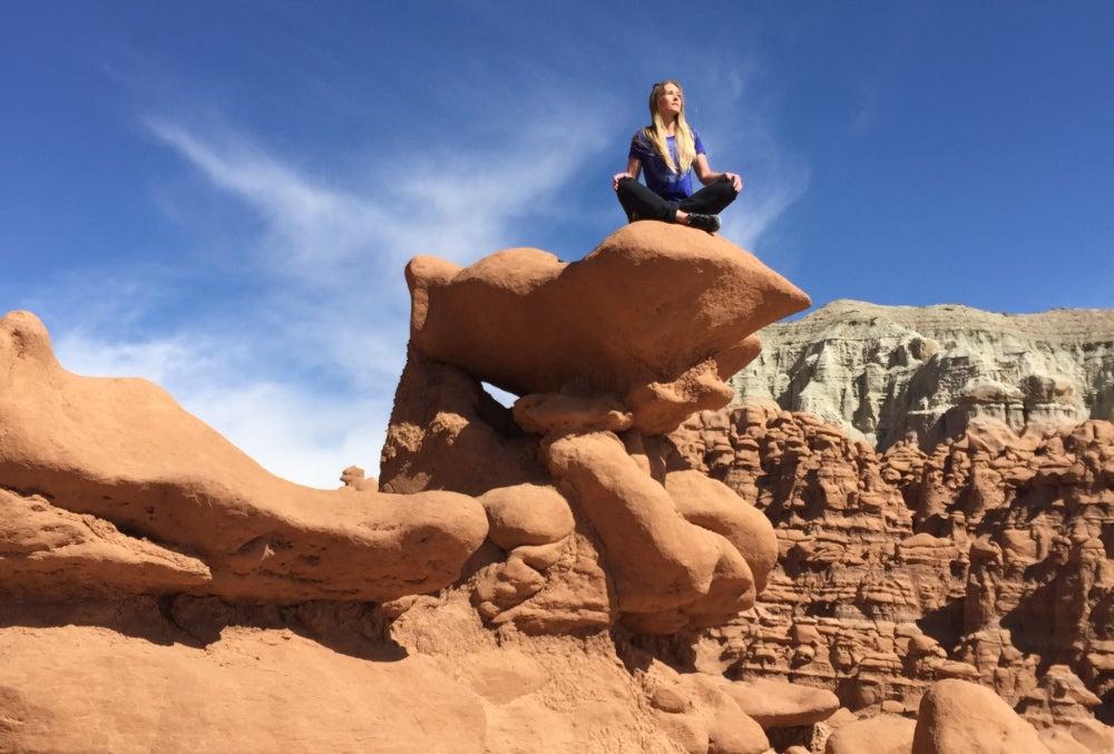 Woman sitting cross legged on rock formation in Goblin Valley