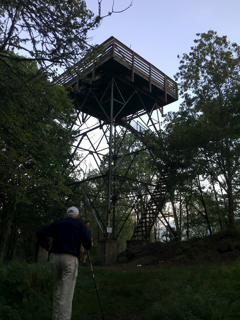 Man hiking in foreground with fire tower and trees visible above him