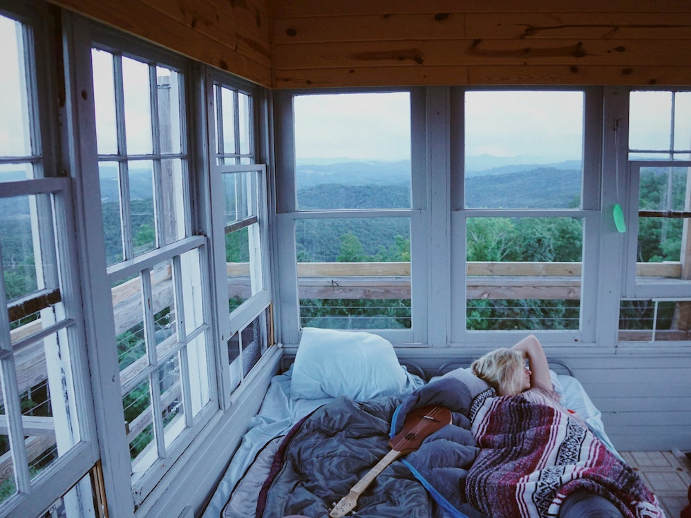 Woman napping in a bed with a ukulele inside of a fire tower