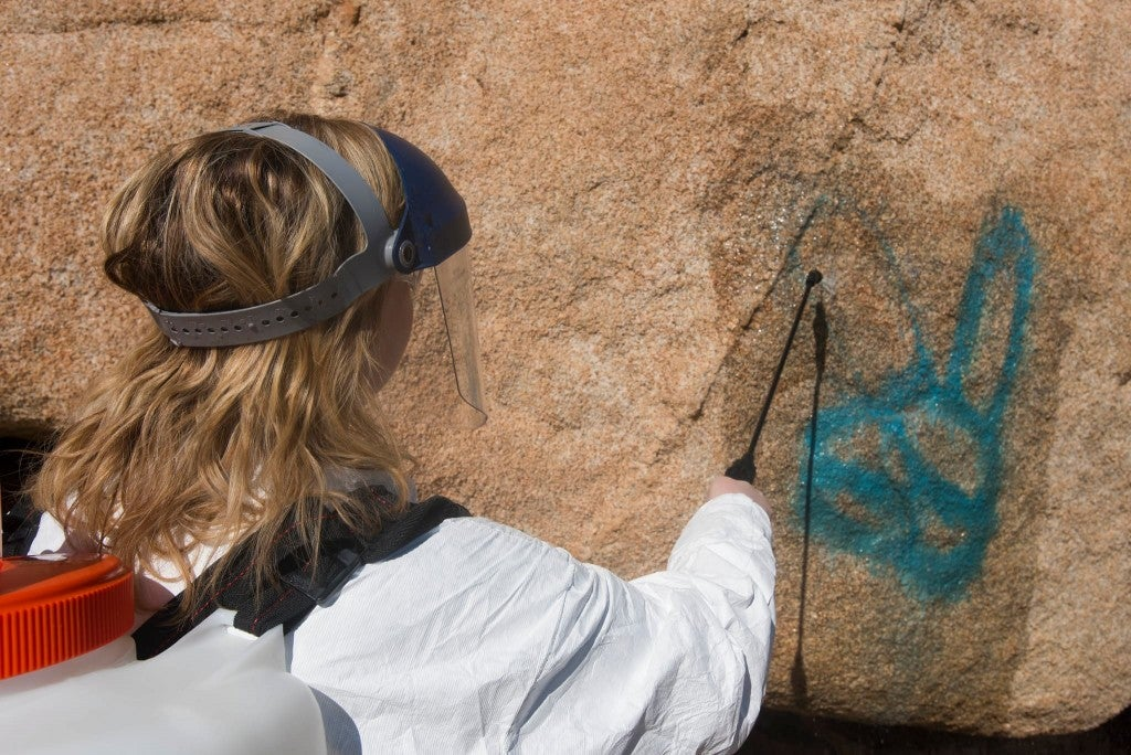 a woman removed graffiti from a red rock face in joshua tree national park