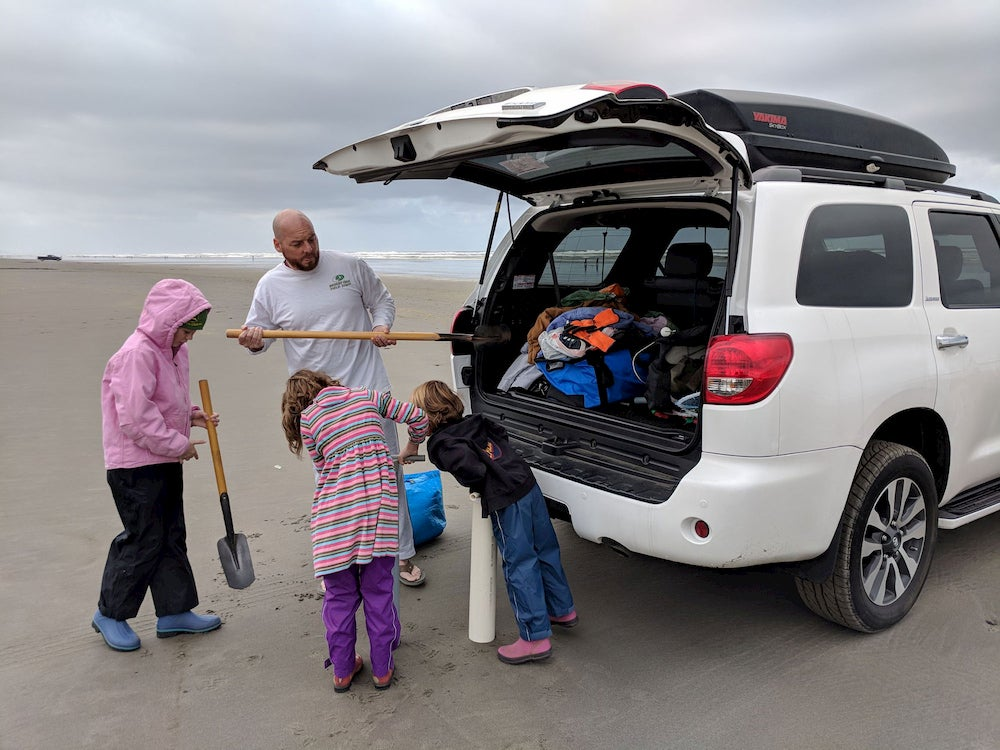 three children look into a car trunk while a man puts a shovel inside