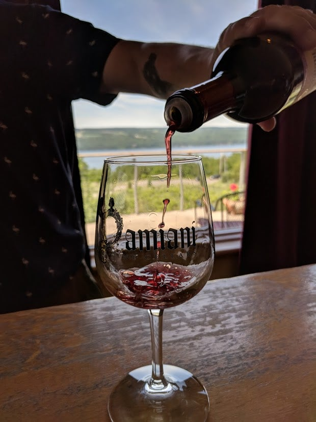 Person pouring wine into a glass
