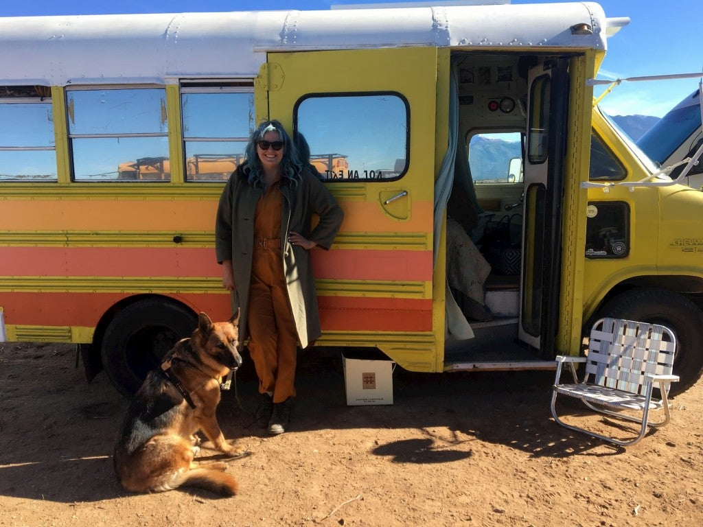 a woman stands next to a converted bus in the desert where she sells custom bathing suits