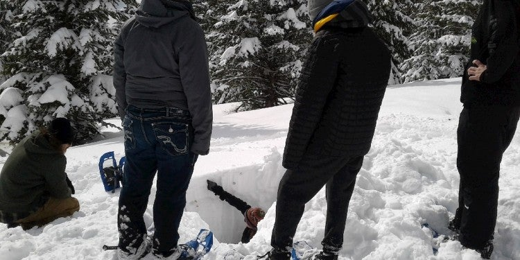 Group of teens gathered around a hole dug in the snow.