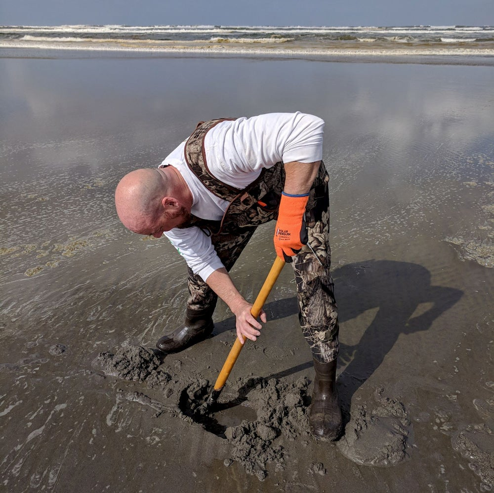 a man digging with a shovel on a beach in washington