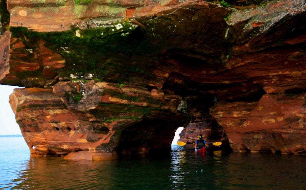 Kayaker paddling under rock formation and cave