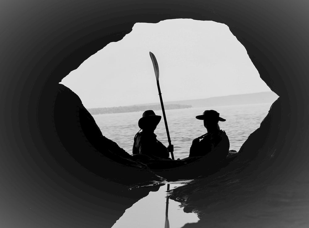 Silhouette of two people in cave with paddle