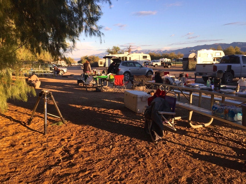 a campsite set up with chairs and picnic tables, and an RV in the background