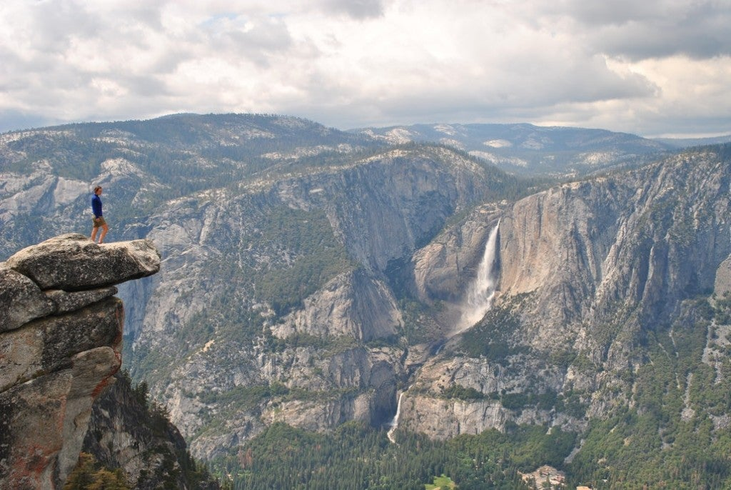 a woman stands on a ledge in Yosemite National Park
