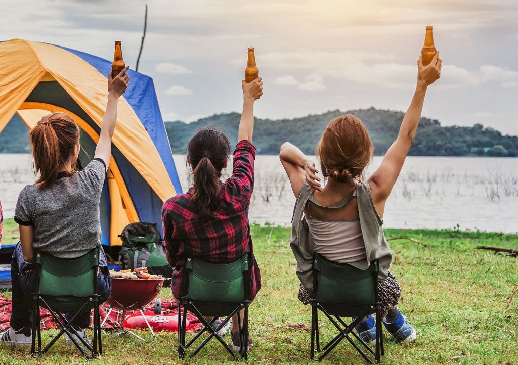 three women holding beers near a tent in chairs while camping