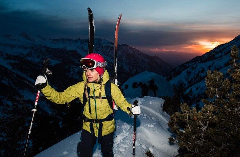 climber caroline gleich holding trekking ples in winter gear climbing a mountain at dawn