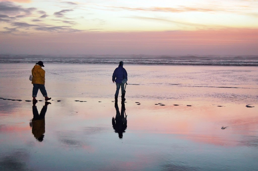 two people wearing rain gear hunting for clams on the beach at dusk