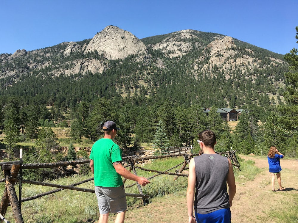 Two men walking along path with mountains in the background while camping in Estes Park