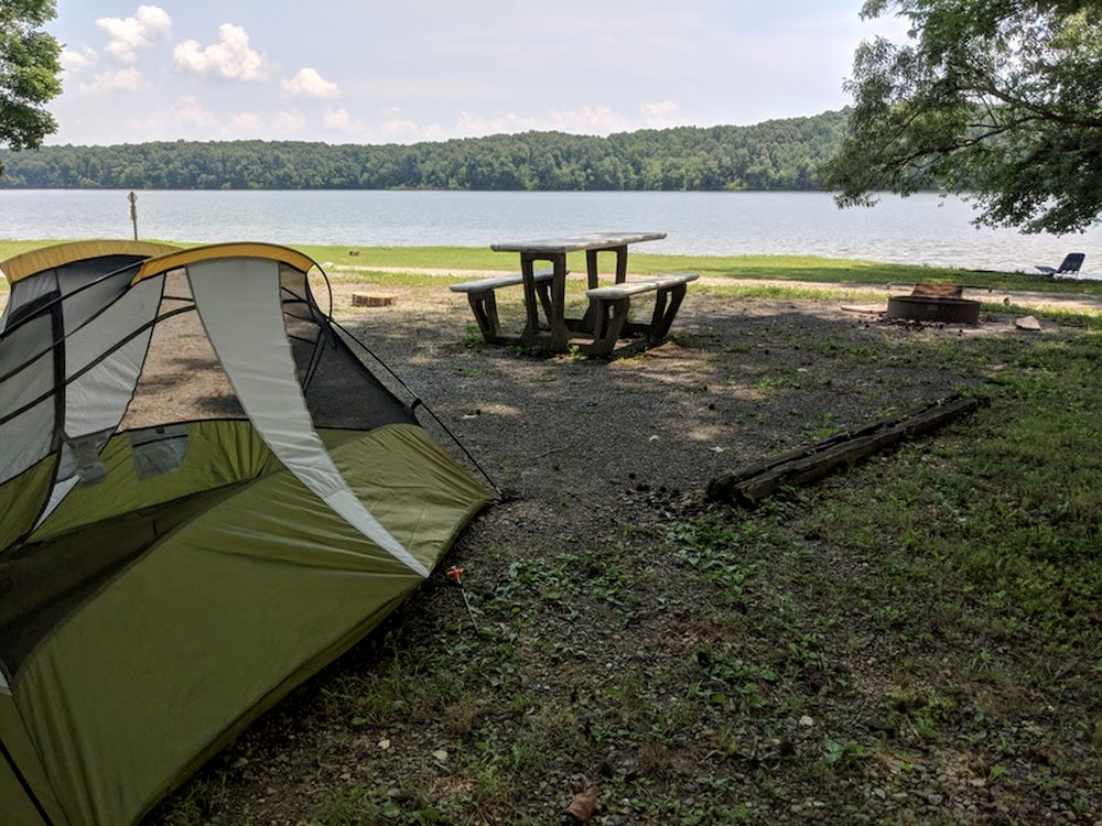 Lakeside campground with picnic table.