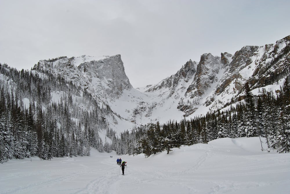 Wide angle shoe of people crossing snowy valley beneath jagged mountains