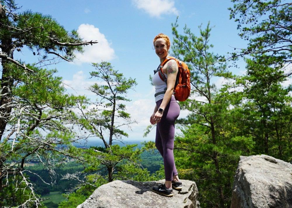 a woman standing on a rock while hiking near lake lanier, ga