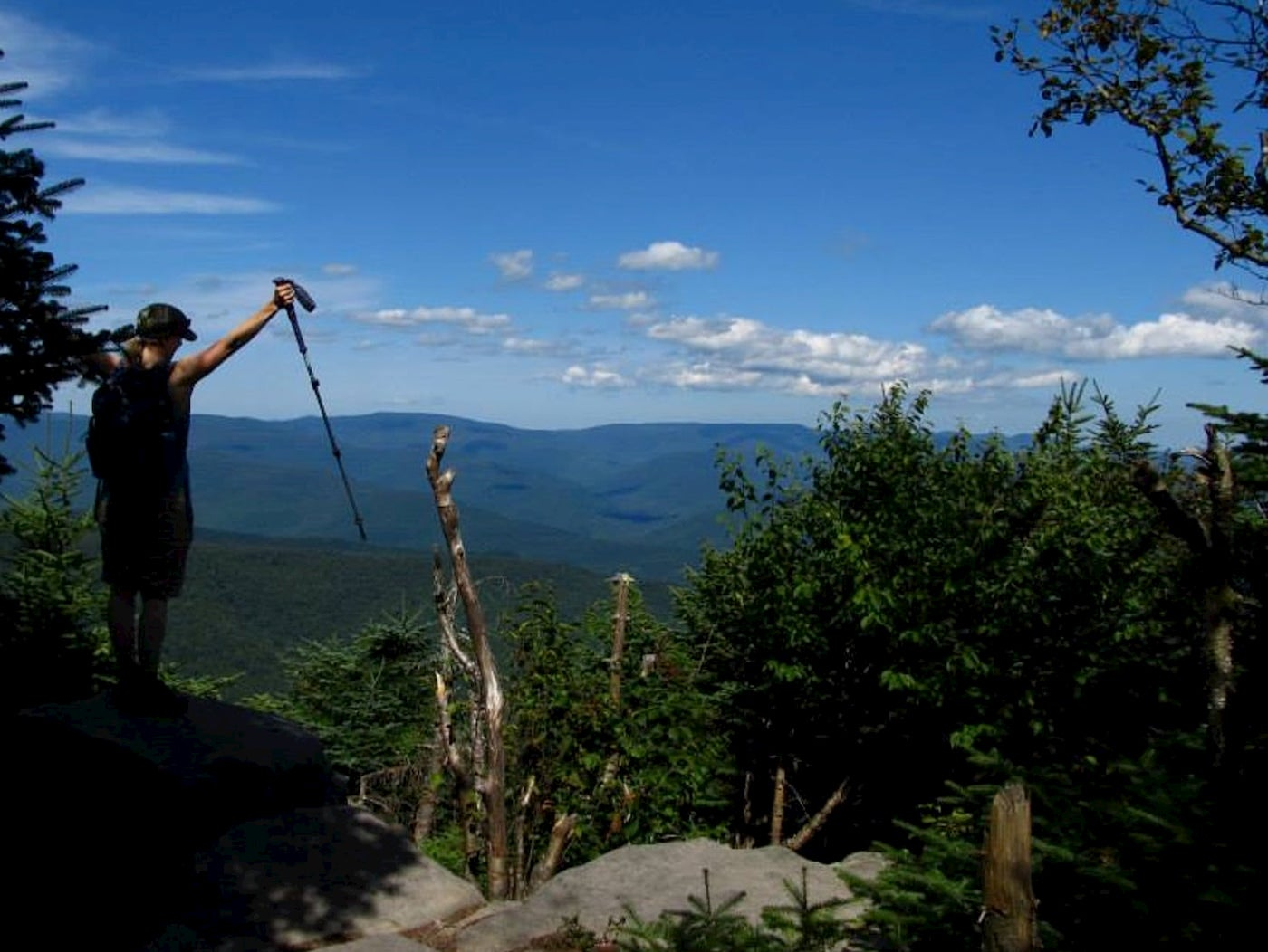 Women hiker standing with trekking poles on the edge of giant ledge.
