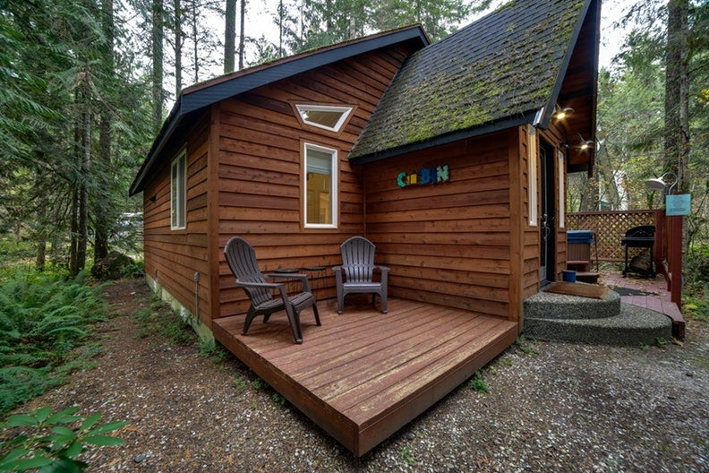 the outside of a mt. baker cabin with adirondack chairs surrounded by trees