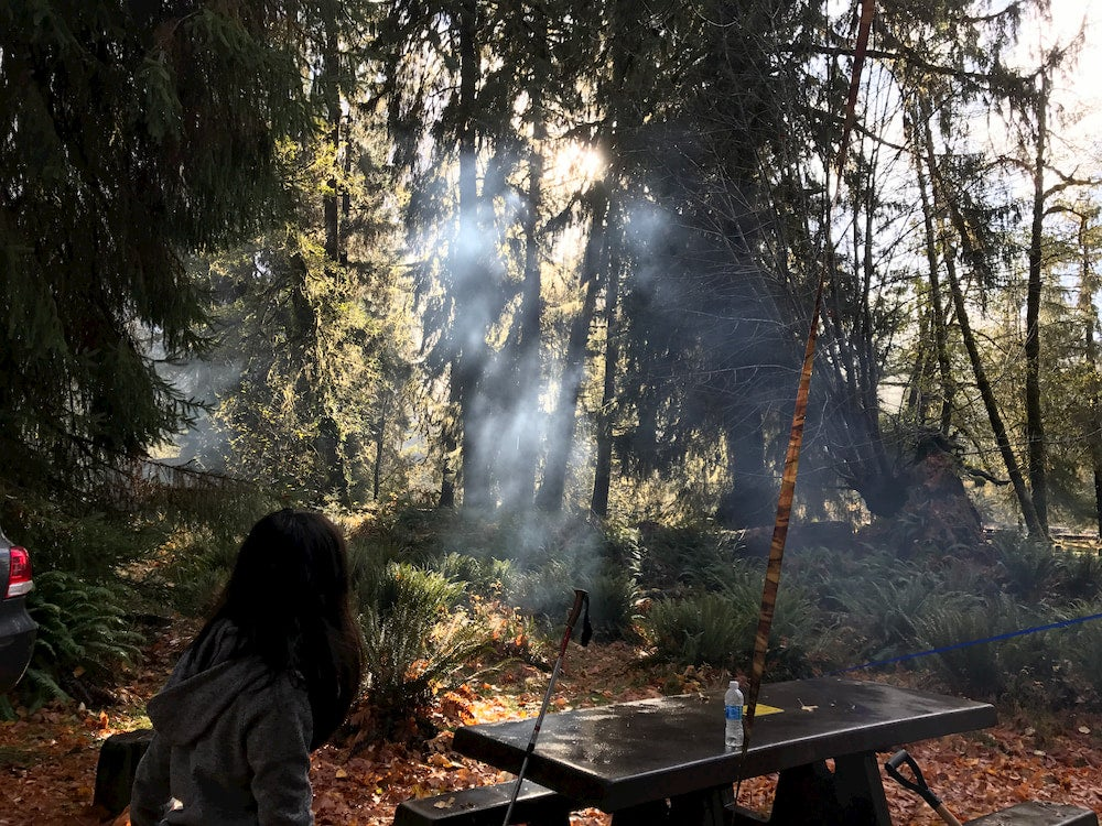 Girl sitting at picnic table in forest with light shining through trees and campfire smoke