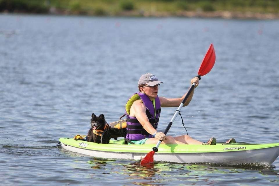 woman paddling kayak on lake with little dog in the back