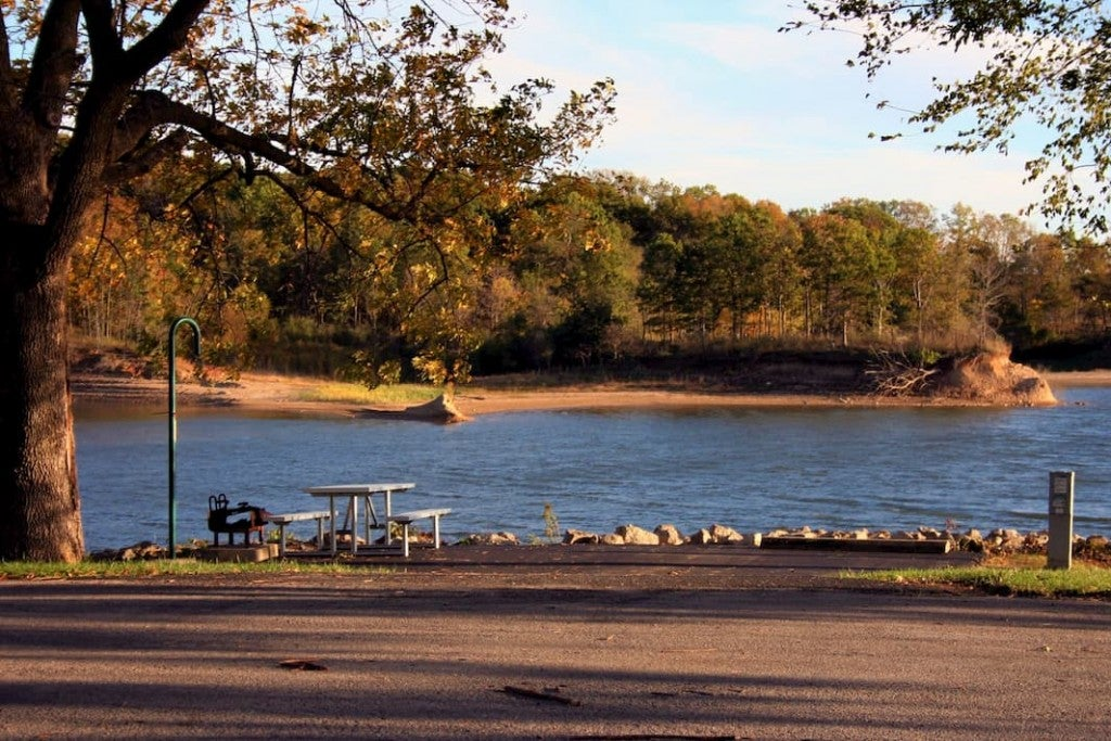 golden sun on lakeside campsite with tent pad and picnic table trees, lake, and sandy lake shore in the distance