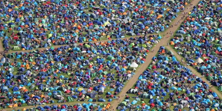 Aerial image of field full of tents camping at a music festival