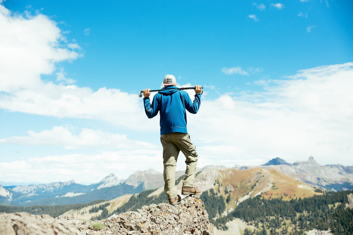 Man standing on top of a mountain in Ouray in the summer.