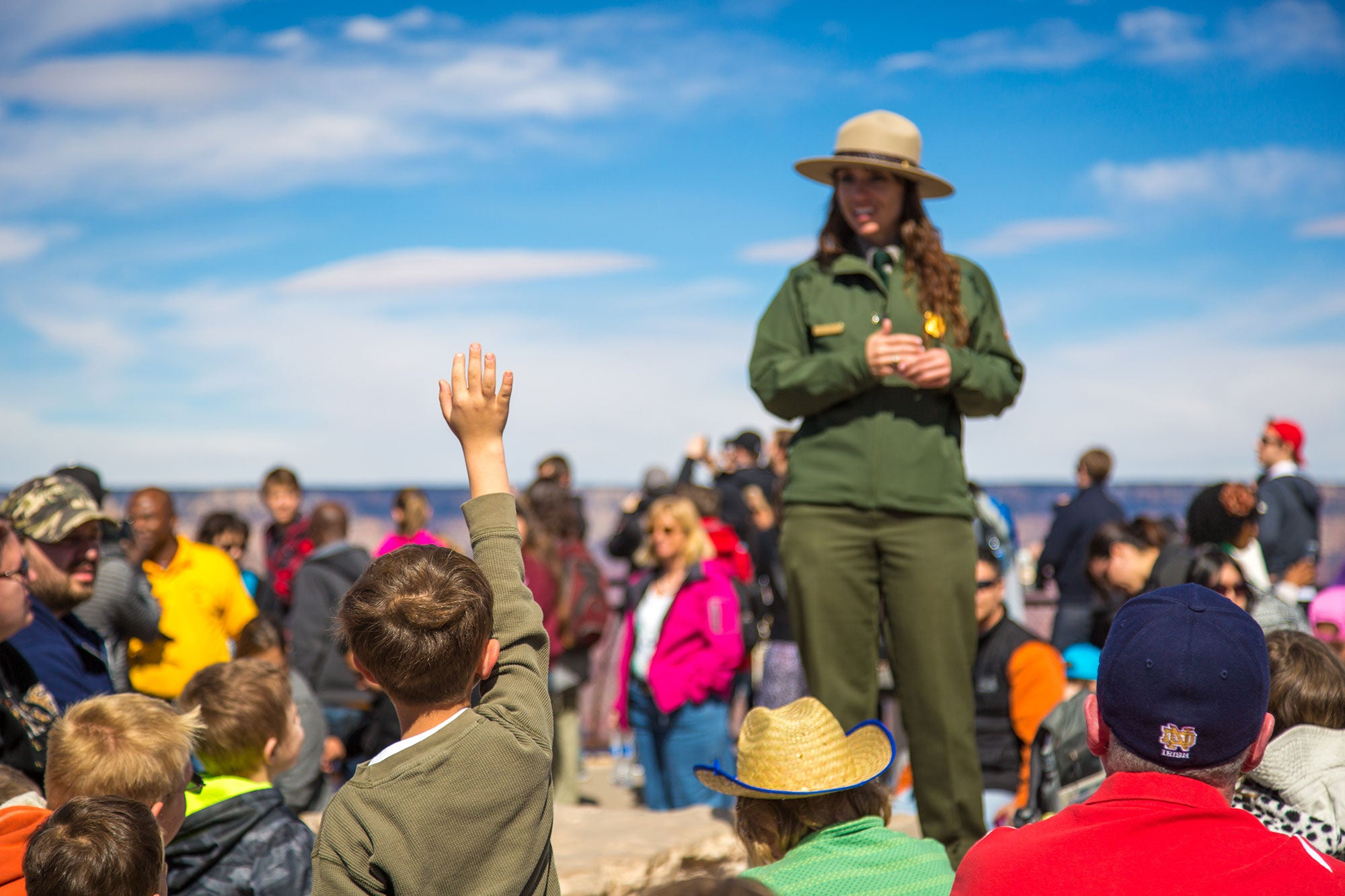 Young boy raises his hand to ask a Park Ranger a question.