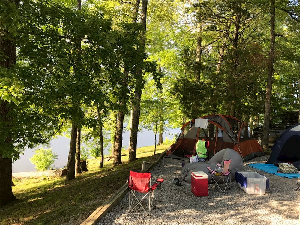 Lakeside campsite in a forested area.