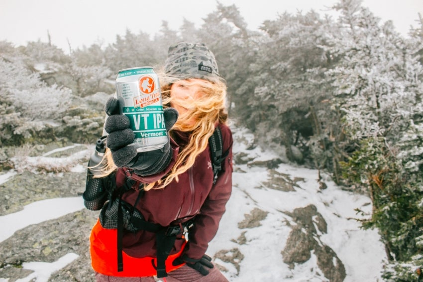 Woman holding Vermont beer with snow and trees in background