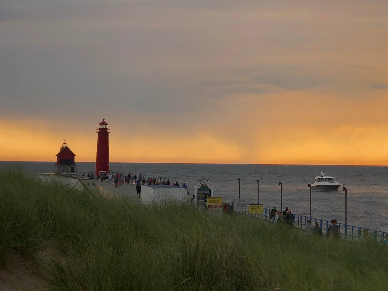 Lighthouse visible at end of crowded beach boardwalk at sunset.