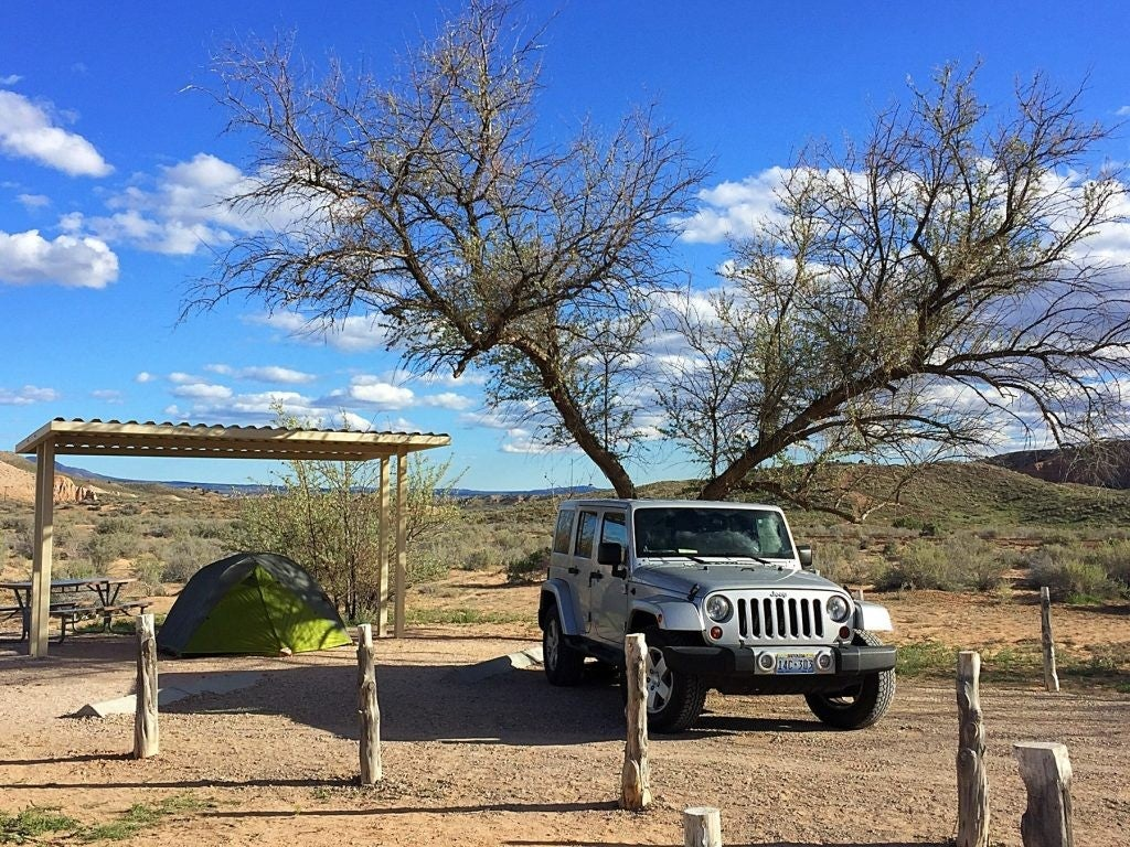 a jeep parked at a campsite with a tent set up in the desert in cathedral gorge state park