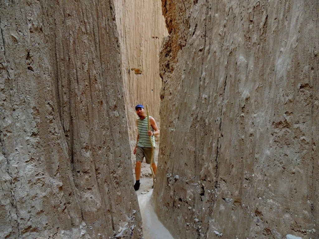 a man peers into a slot canyon in cathedral gorge state park