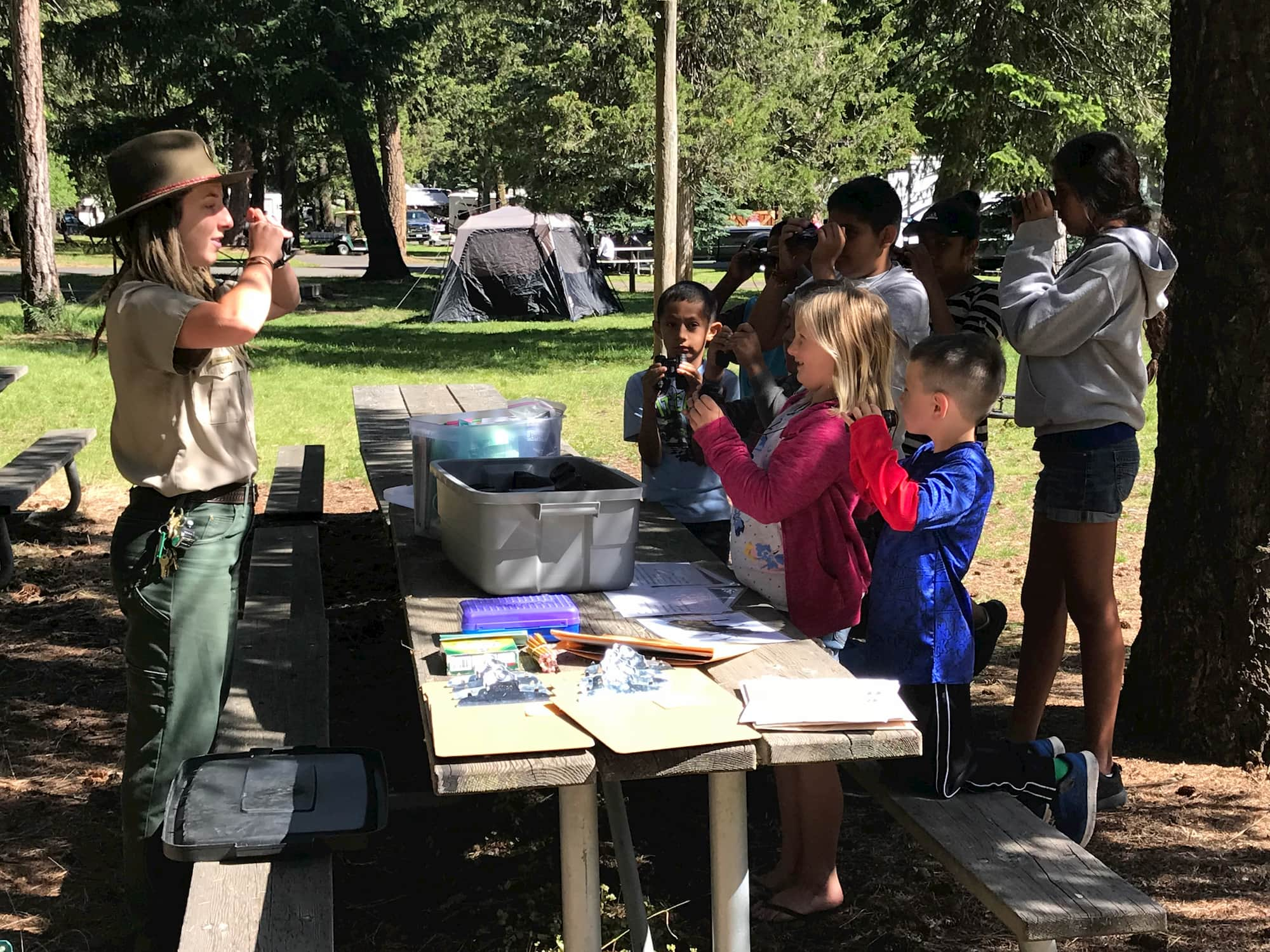 a ranger at a national park swears in childern participating in a junior ranger program