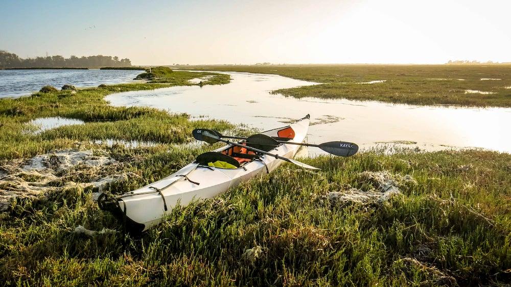 an oru kayak on a swamp at dusk