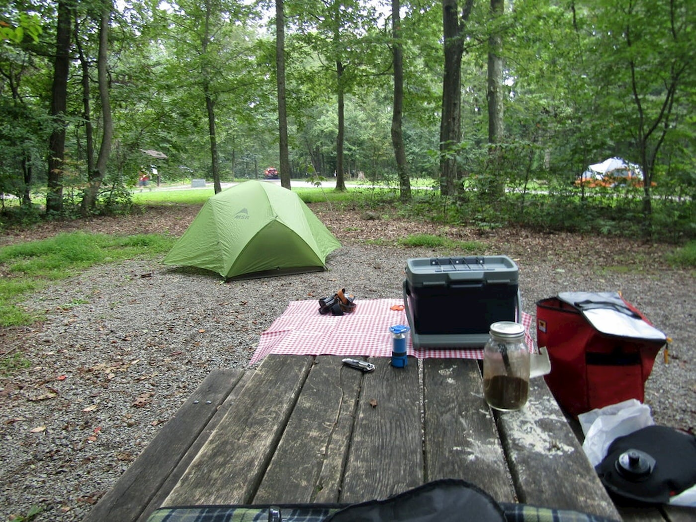 Campsite with picnic table and tent in forested area.