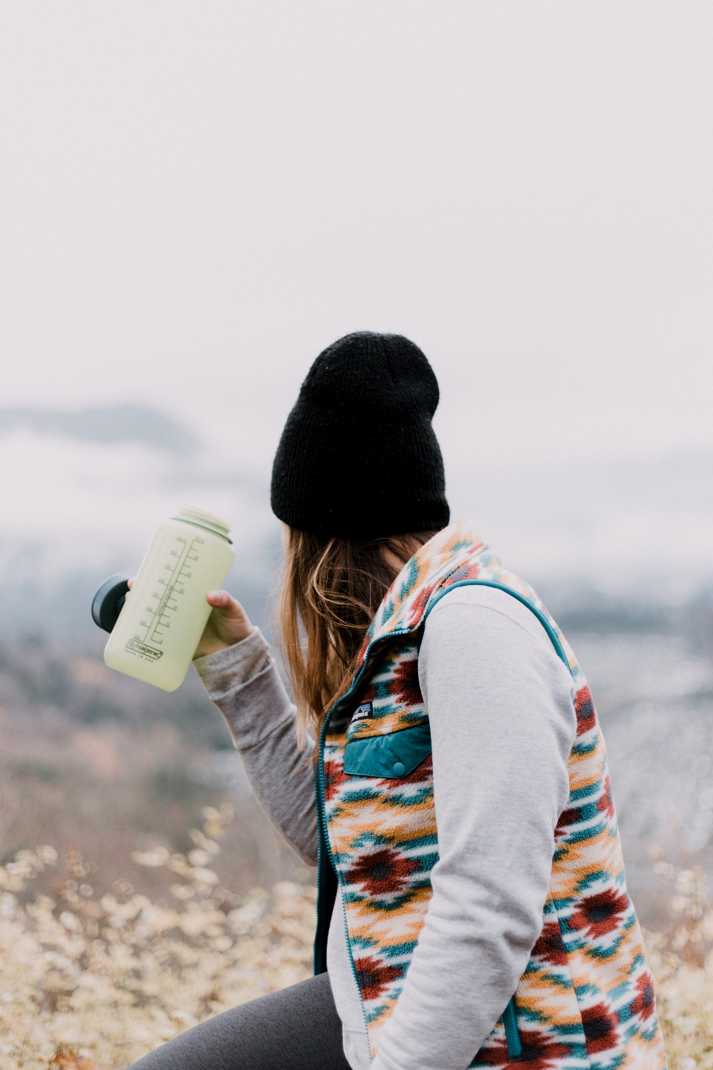 Women wearing outdoors brands in layers and drinking water out of a nalgene.