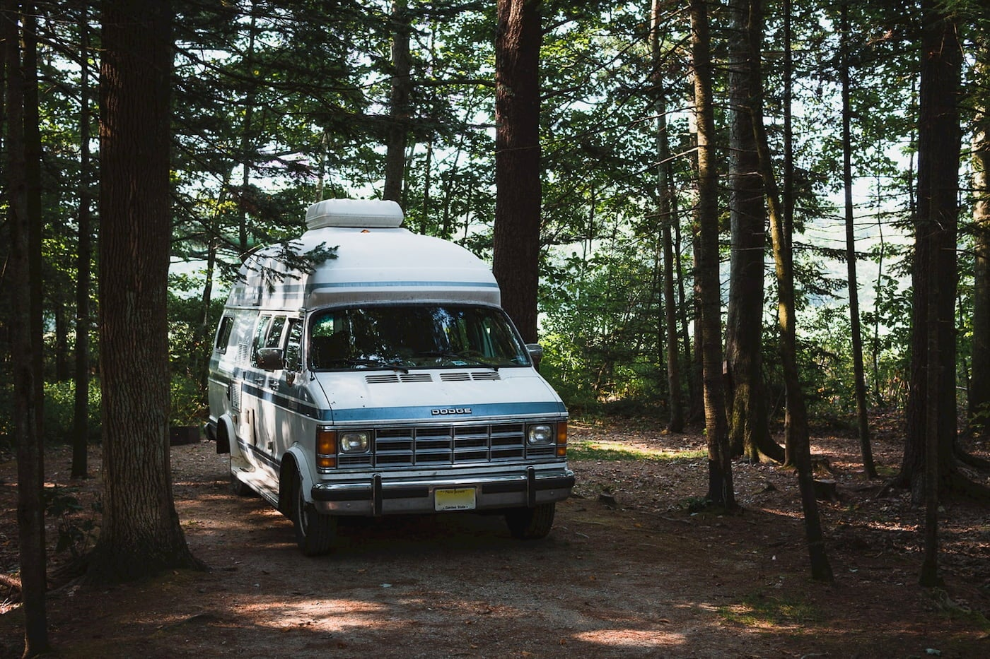 Dodge van parked in a wooded campsite with water in the background.