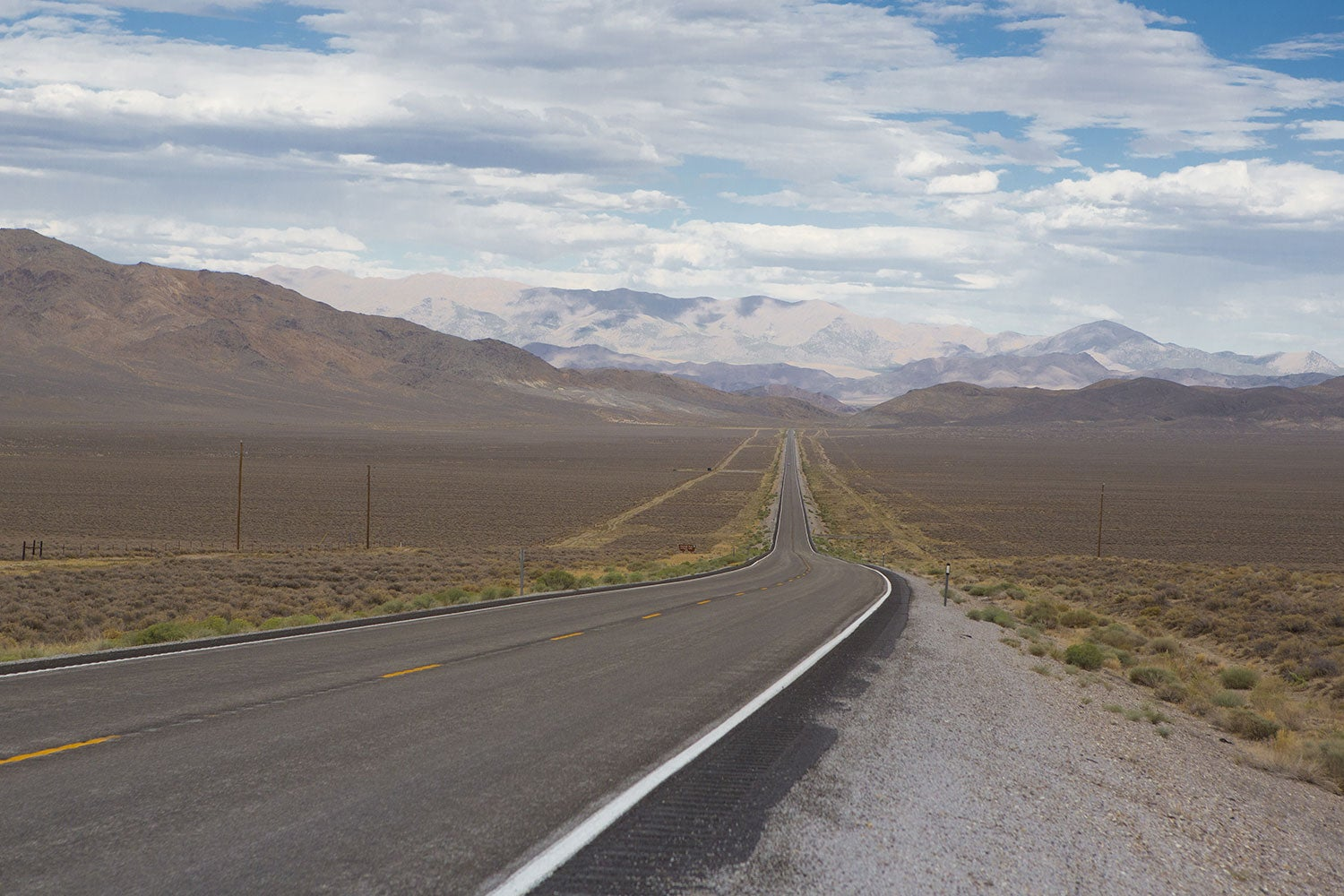 a stretch of Route 50, cutting through featureless, brown landscape with mountains in the distance.