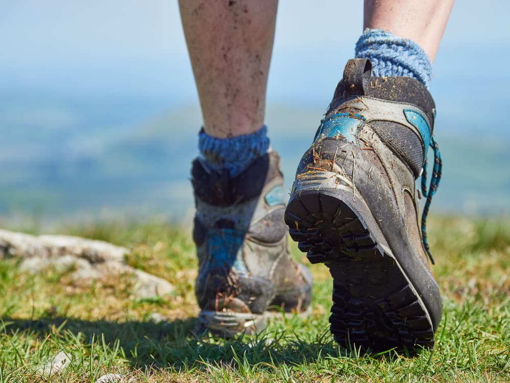 close up of hiker's dirty legs and boots while walking