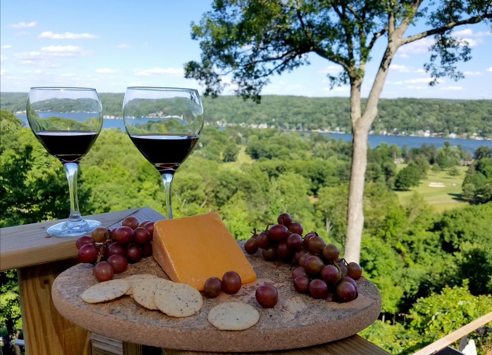 View of valley and wine, cheese and grapes in foreground