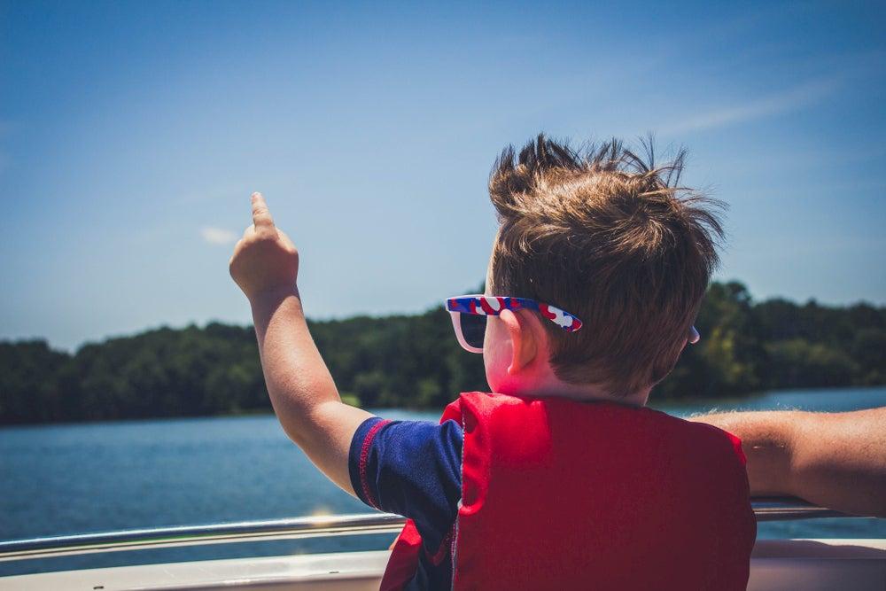Boy on boat pointing at lake