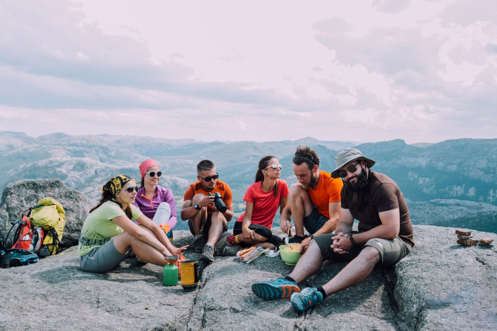 6 hiker friends eating lunch on a mountain surrounded by gear