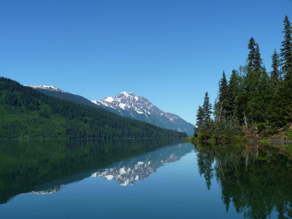 Lake reflecting mountain with trees on far right edge of lake